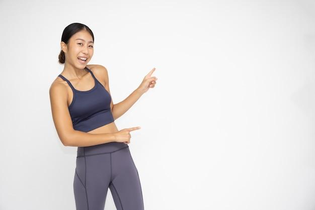 Azjatyckie sportowe dziewczyny stojące i wskazujące palcem na bok puste miejsce na kopię