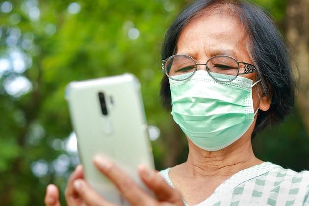 Azjatyckie starsze kobiety noszące zielone maski stojące w ogrodzie, trzymające smartfona rozmawiaj online za pośrednictwem połączenia wideo. koncepcja ochrony przed koronawirusem. dystans społeczny