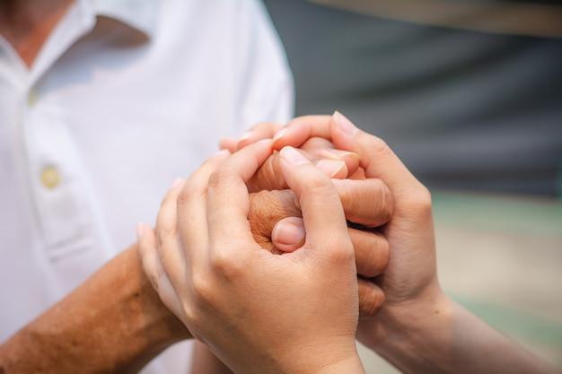 Azjatyckie starszy i azjatyckie młode trzymając się za ręce.