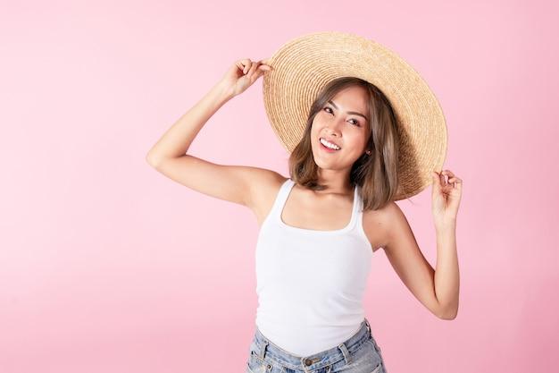Azjatyckie turyści noszą letnie ubrania i słomkowe kapelusze z szerokim rondem