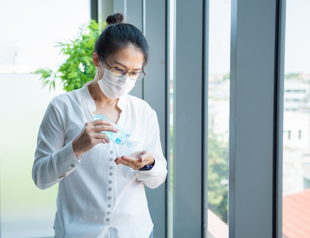 Azjatyckie żeńskie poważne myśli i odzieży maski przy wzorcowym nowym biurowym wyglądają przez okno