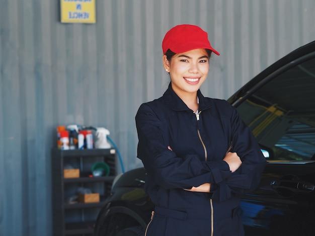 Azjatyckiego kobieta pracownika płuczkowy samochód przy garażem