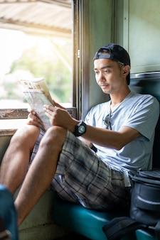 Azjatyckiego mężczyzna backpacker czytania podróżna mapa siedzi na starym taborowym siedzeniu przy tajlandia