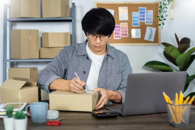 Azjatyckiego mężczyzna przedsiębiorcy małego biznesu przedsiębiorcy mśp początkowy niezależny mężczyzna pracuje z pudełkiem online marketing pakuje i doręczeniowa scena ministerstwo spraw wewnętrznych w domu, onlinebusiness sprzedawcy pojęcie.