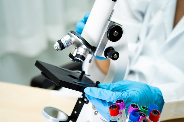 Azjatyckiego naukowa biochemika pracujący badanie z mikroskopem w laboratorium.