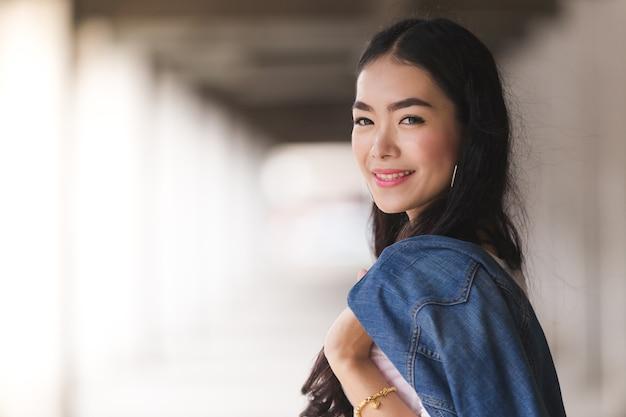 Azjatyckiego portreta śliczna młoda dziewczyna cajgi w budynku
