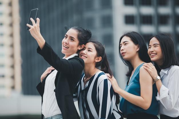 Azjatyckiego stylu życia bizneswoman najlepsi przyjaciele ono uśmiecha się i ma zabawy chodzącego selfie przy miastem
