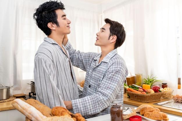 Azjatyckiej homoseksualnej pary kulinarny śniadanie przy kuchnią w ranku