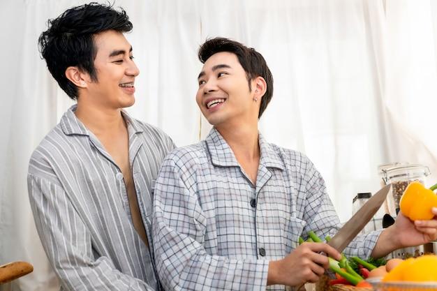 Azjatyckiej homoseksualnej pary szczęśliwa i śmieszna kulinarna sałatka przy kuchnią