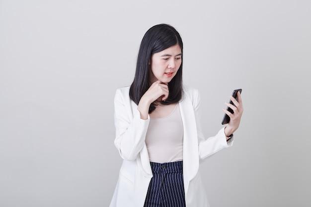 Azjatyckiej kobiety mienia myślący telefon komórkowy