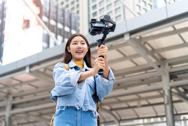 Azjatyckiej kobiety turystycznej podróży vlogger bierze selfie wideo w mieście