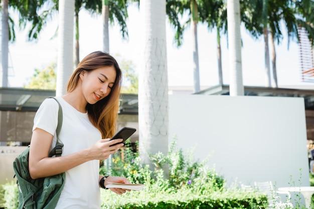 Azjatyckiej kobiety turystyczny backpacker uśmiecha się smartphone podróżuje samotnie i używa