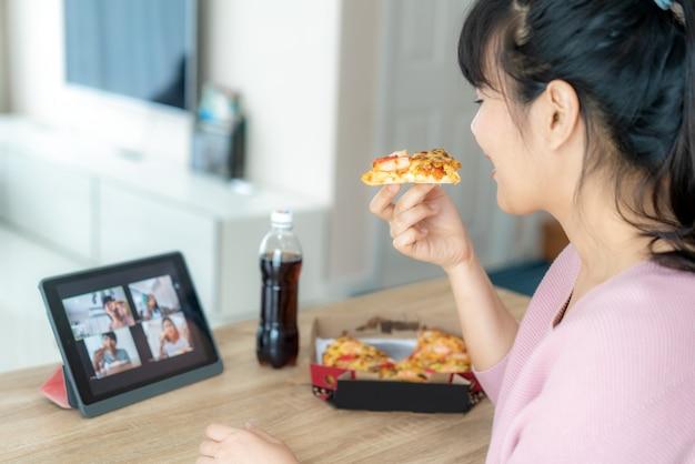 Azjatyckiej kobiety wirtualnej szczęśliwej godziny spotkania przyjęcie i łasowanie jedzenie online wpólnie