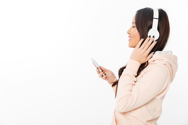 Azjatyckiej rozochoconej kobiety słuchająca muzyka z hełmofonami.