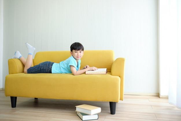 Azjatyckiej ślicznej chłopiec czytelniczy podręcznik i pościel na kanapie.