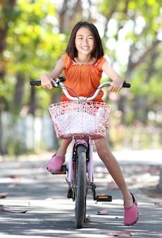 Azjatyckiej ślicznej małej dziewczynki jeździecki bicykl plenerowy