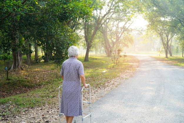Azjatyckiej starszej kobiety cierpliwy spacer z piechurem w parku.