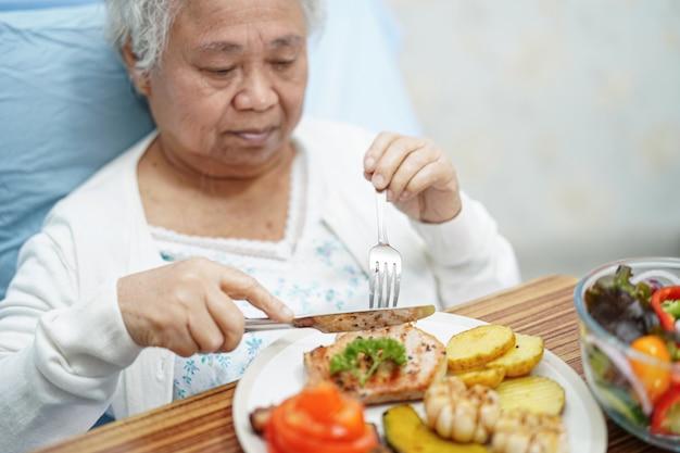 Azjatyckiej starszej kobiety łasowania cierpliwy śniadanie na łóżku w szpitalu.
