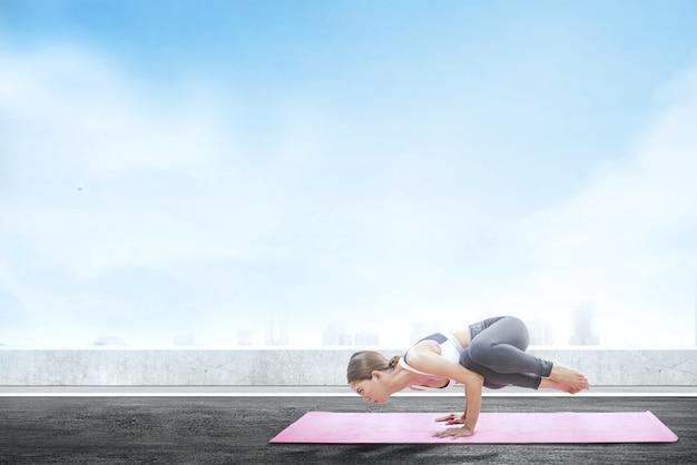 Azjatyckiej zdrowej kobiety ćwiczy joga na dywanie przy dachu tłem