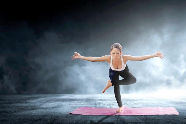 Azjatyckiej zdrowej kobiety ćwiczy joga na dywanie przy salowym
