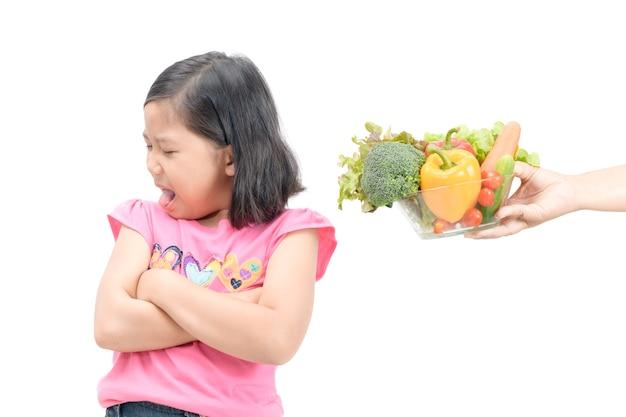 Azjatykcia dziecko dziewczyna z wyrażeniem niesmak przeciw warzywom odizolowywającym na białym tle, refusin