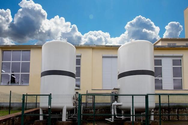 Azot ciekły w dwóch zbiornikach magazynowych na zewnątrz budynku przemysłowego. zbiorniki są ogrodzone płotem ochronnym, aby zapobiec wypadkom.