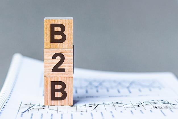 B2b - business to business - akronim na drewnianych kostkach na powierzchni kolumn liczb