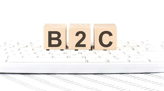 B2c - drewniany klocek na tle klawiatury z wykresem