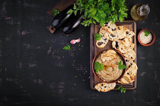 Baba ghanoush wegański hummus z bakłażana z przyprawami, pietruszką i grzankami. baba ganoush. kuchnia bliskowschodnia. widok z góry, z góry