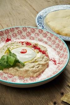 Baba ghanoush z bliska - zakąska lewantyńska z tłuczonego gotowanego bakłażana zmieszanego z tahini z sosem jogurtowym w płycie ceramicznej na drewnianej powierzchni