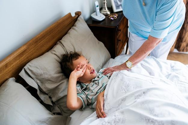 Babcia budzi swojego wnuka z łóżka