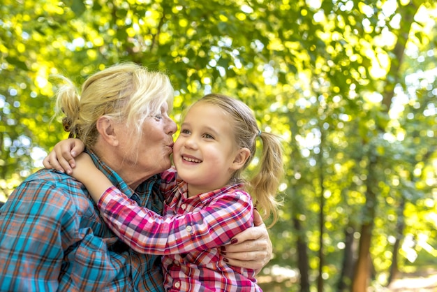 Babcia całuje swoją śliczną wnuczkę w parku w słoneczny dzień