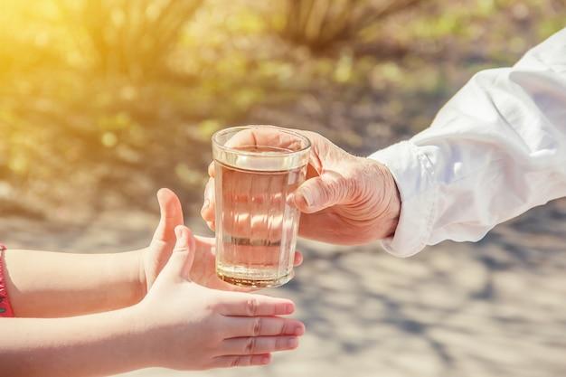 Babcia daje szklankę czystej wody dla dziecka. selektywna ostrość.
