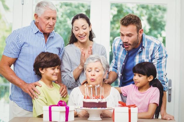 Babcia dmuchanie świeczki urodzinowe z rodziną