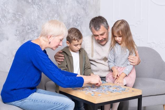 Babcia, dziadek i wnuczka zbierają puzzle przy stole w salonie. szczęśliwa rodzina spędza czas razem, grając w gry edukacyjne
