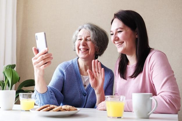 Babcia i córka komunikują się z przyjaciółmi za pośrednictwem połączenia wideo i dobrze się bawią
