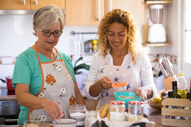 Babcia i córka w domu gotują i uśmiechają się - ciesząc się i baw się razem w domu - córka pije, a babcia pokazuje, jak gotować rybę