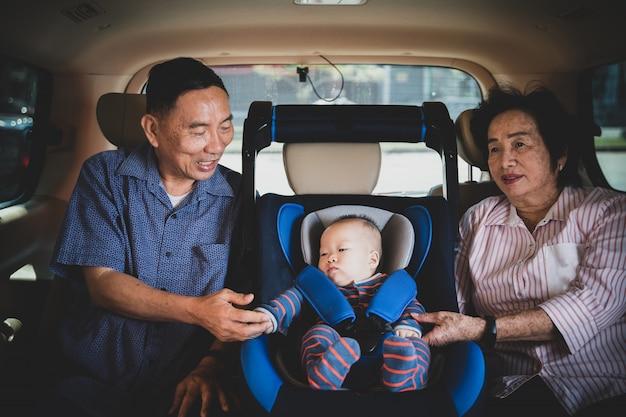 Babcia i dziadek dbają o swoją małą wnuczkę w samochodzie, pomagają jej i kibicują