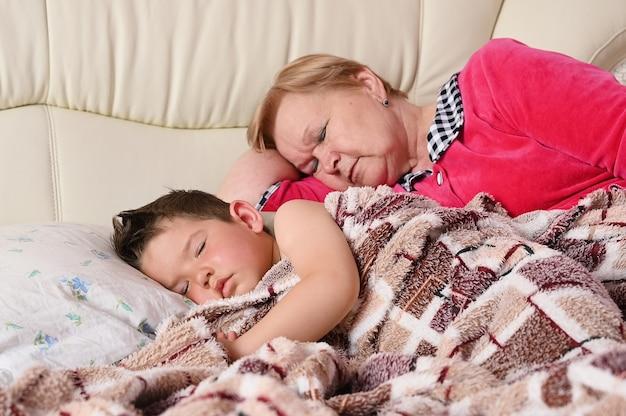 Babcia i dziecko odpoczywają na łóżku