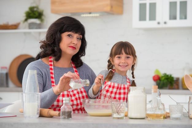 Babcia i mała wnuczka z warkoczykami w fartuchach kucharskich gotują razem w kuchni ubijaj i solij mieszankę jajeczną
