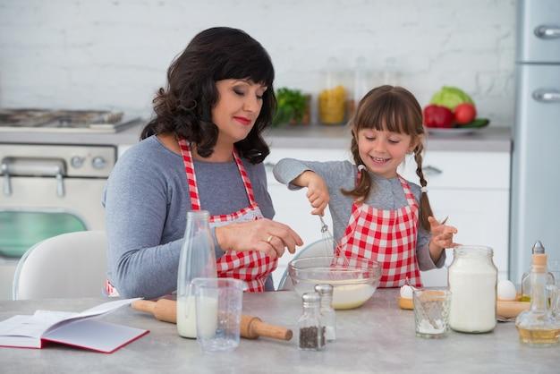 Babcia i mała wnuczka z warkoczykami w kucharskich fartuchach gotują razem w kuchni ubijając mieszankę jajeczną szczęśliwa rodzina