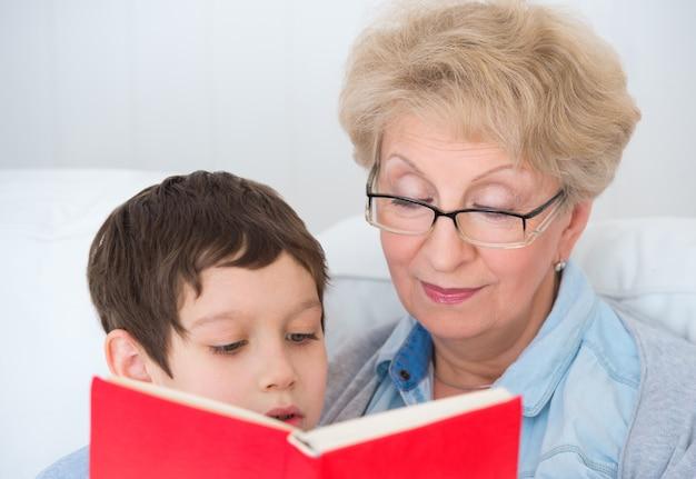 Babcia i mały chłopiec czytanie książki szczęśliwy razem w domu