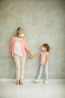 Babcia i śliczna mała wnuczka w maskach oddechowych
