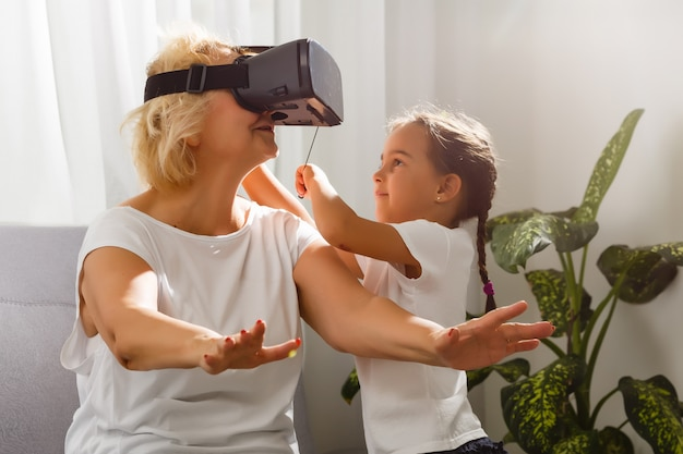 Babcia i wnuczka bawi się goglami wirtualnej rzeczywistości