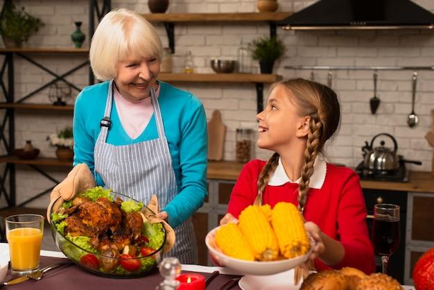 Babcia i wnuczka patrzą na siebie i trzymają jedzenie