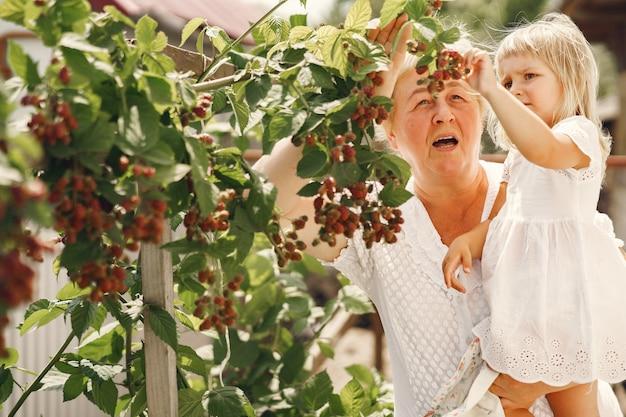 Babcia i wnuczka razem przytulają się i radośnie śmieją się latem w kwitnącym ogrodzie. rodzinny styl życia na świeżym powietrzu.