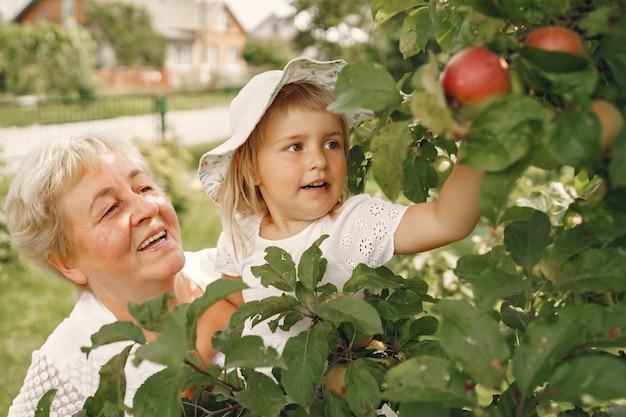 Babcia i wnuczka razem przytulające się i radośnie śmiejące się w kwietniowym ogrodzie kwitnących moreli. rodzinny styl życia na świeżym powietrzu.