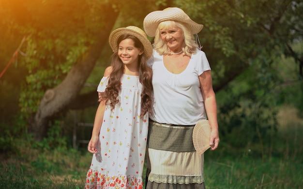 Babcia i wnuczka stoją w pięknym ogrodzie