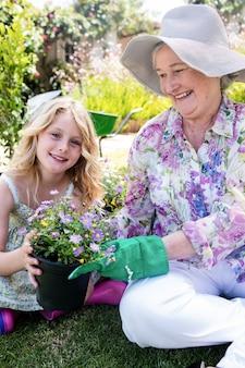 Babcia i wnuczka trzyma doniczkę