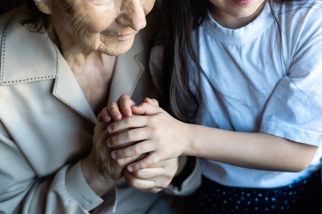 Babcia i wnuczka trzymając się za ręce.